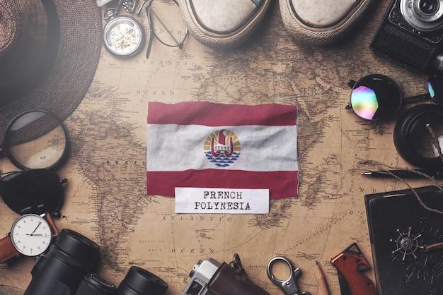 Bandeira da polinésia francesa entre os acessórios do viajante no antigo mapa vintage. tiro aéreo