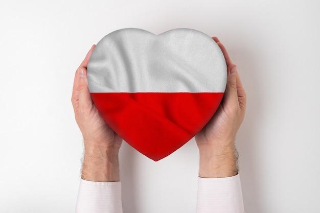 Bandeira da polônia em uma caixa em forma de coração nas mãos masculinas. fundo branco