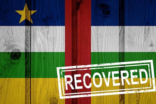 Bandeira da república centro-africana que sobreviveu ou se recuperou das infecções da epidemia do vírus corona ou coronavírus. bandeira do grunge com selo recuperado