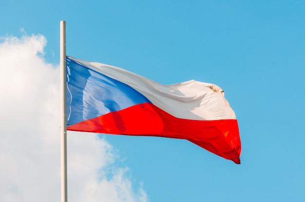 Bandeira da república checa colorida no céu azul.