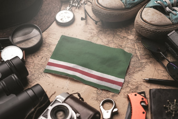 Bandeira da república chechena da ichkeria entre acessórios do viajante no antigo mapa vintage. conceito de destino turístico.