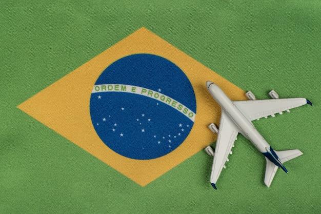Bandeira da república federativa do brasil e modelo de avião. abrindo fronteiras após quarentena. voos da mesatlantica