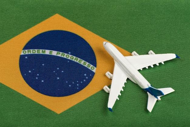 Bandeira da república federativa do brasil e modelo de avião. abrindo fronteiras após quarentena. voos de mesoatlantica