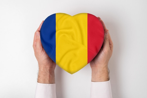 Bandeira da romênia em uma caixa em forma de coração nas mãos masculinas.
