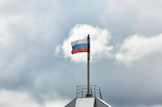 Bandeira da rússia contra o fundo do céu nublado. bandeira russa acenando no mastro