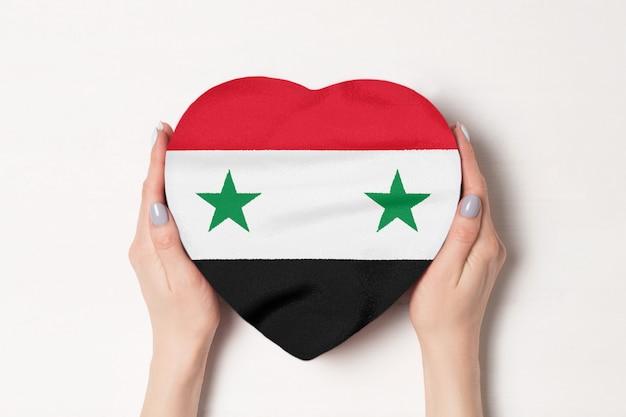 Bandeira da síria em uma caixa em forma de coração nas mãos femininas.