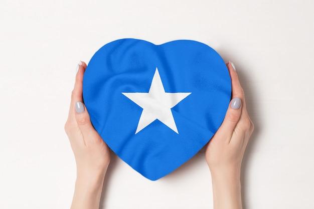 Bandeira da somália em uma caixa em forma de coração nas mãos femininas. fundo branco