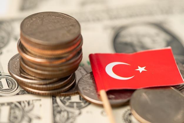 Bandeira da turquia com moedas no fundo de notas de dólar.