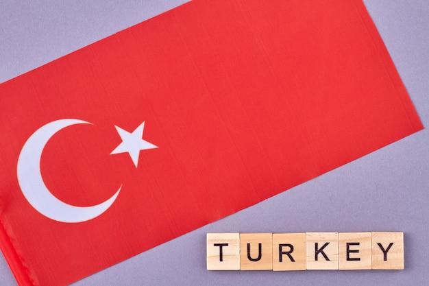Bandeira da turquia. simbólico turco nacional. palavra de turquia feita de blocos de letras de madeira. isplated em fundo roxo.