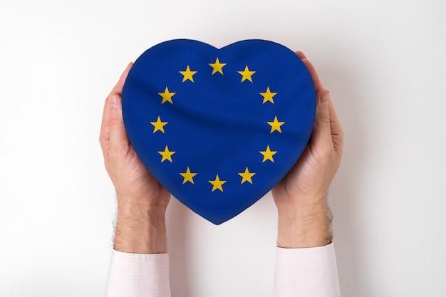Bandeira da ue em uma caixa em forma de coração nas mãos masculinas. fundo branco