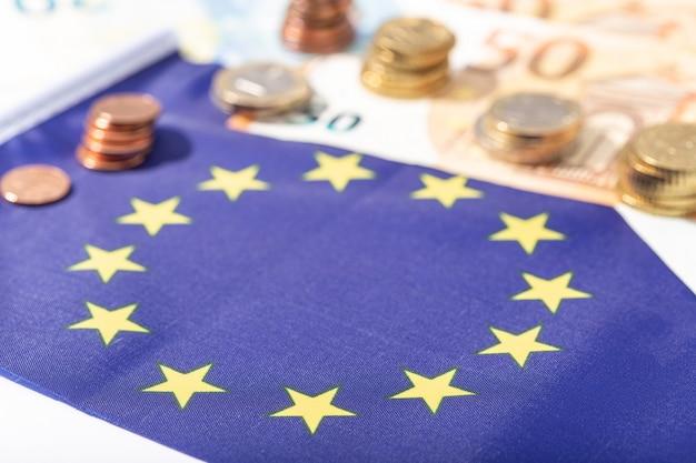 Bandeira da união europeia com notas e moedas de euro
