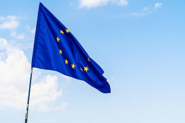 Bandeira da união europeia contra o céu azul acenando