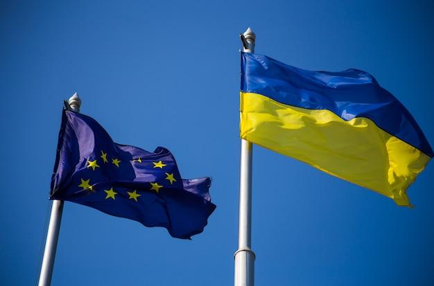 Bandeira da união europeia e bandeira da ucrânia tremulando contra o céu azul
