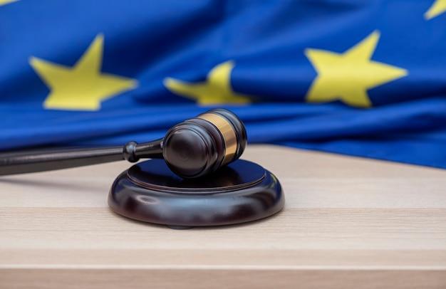 Bandeira da união europeia e martelo de madeira de juízes no topo, imagem conceitual sobre tribunal e justiça