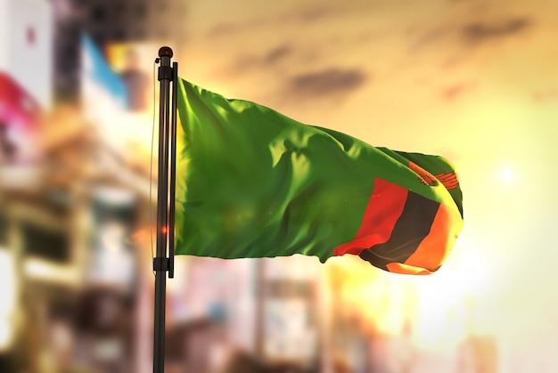 Bandeira da zâmbia contra a cidade fundo borrado no amanhecer luz de fundo