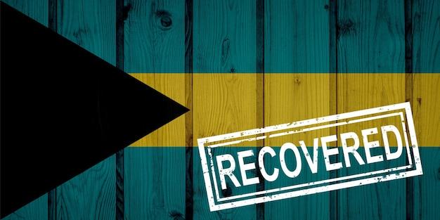 Bandeira das bahamas que sobreviveu ou se recuperou das infecções da epidemia do vírus corona ou coronavírus. bandeira do grunge com selo recuperado