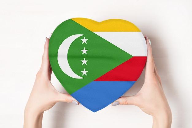 Bandeira das comores em uma caixa em forma de coração nas mãos femininas.
