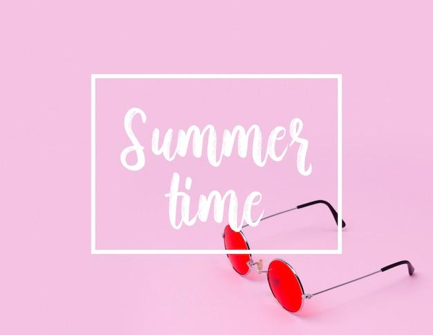Bandeira das horas de verão com os óculos de sol vermelhos no fundo cor-de-rosa.