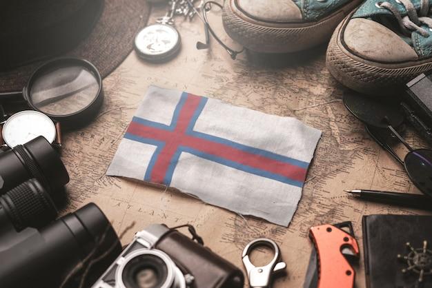 Bandeira das ilhas faroé entre acessórios do viajante no antigo mapa vintage. conceito de destino turístico.