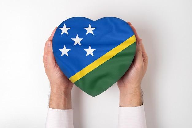 Bandeira das ilhas salomão em uma caixa em forma de coração nas mãos masculinas.