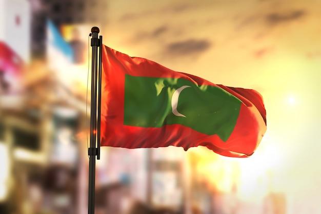 Bandeira das maldivas contra a cidade fundo borrado no amanhecer luz de fundo