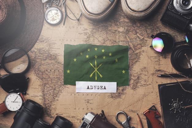 Bandeira de adygea entre acessórios do viajante no mapa antigo do vintage. tiro aéreo