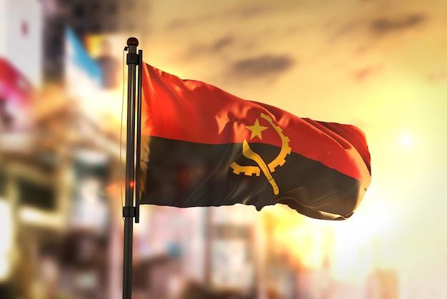Bandeira de angola contra a cidade fundo borrado no amanhecer luz de fundo
