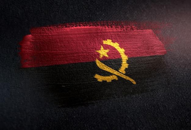 Bandeira de angola feita de tinta de pincel metálico na parede escura de grunge