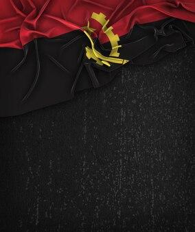 Bandeira de angola vintage em um quadro preto de grunge com espaço para texto