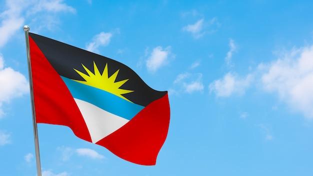 Bandeira de antígua e barbuda na pole. céu azul. bandeira nacional de antígua e barbuda