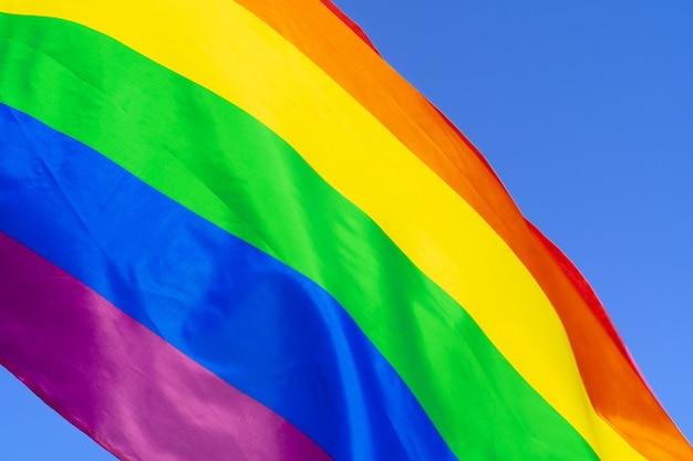 Bandeira de arco-íris gay balançando ao vento em um céu azul claro