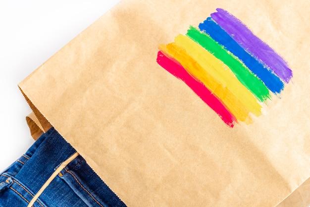 Bandeira de arco-íris lgbt pintada em uma sacolinha de papel com jeans