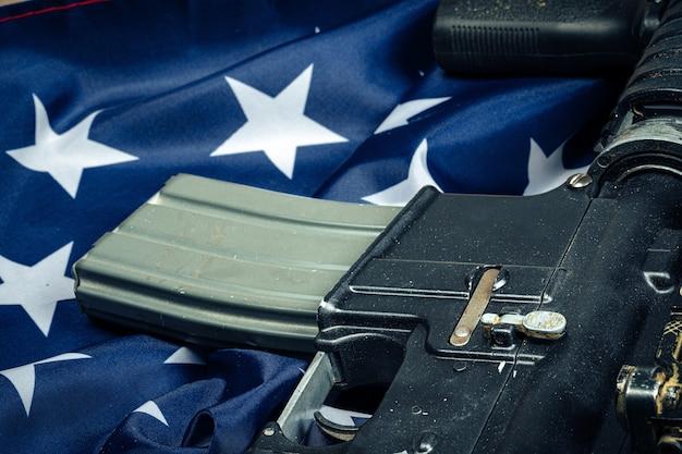 Bandeira de batalha dos eua e espingarda de assalto na mesa de madeira.