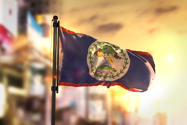 Bandeira de belize contra a cidade fundo borrado no amanhecer luz de fundo