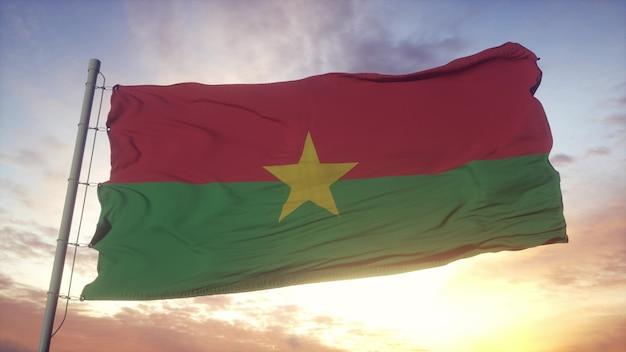 Bandeira de burkina faso balançando ao vento, o céu e o sol de fundo. renderização 3d.