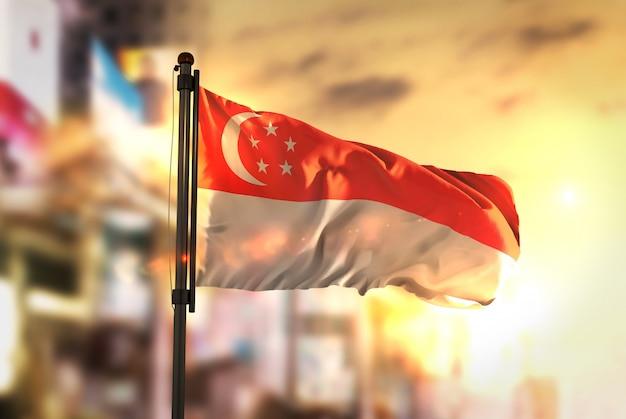 Bandeira de cingapura contra a cidade fundo borrado no amanhecer luz de fundo