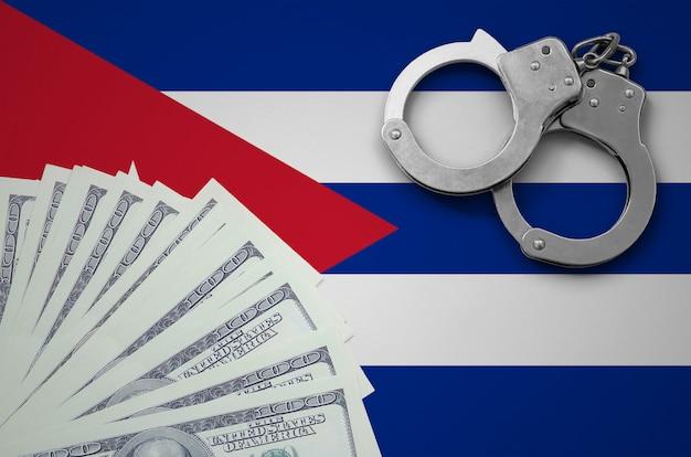 Bandeira de cuba com algemas e um pacote de dólares. o conceito de operações bancárias ilegais em moeda americana