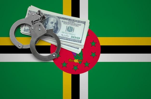 Bandeira de dominica com algemas e um maço de dólares. o conceito de infringir a lei e crimes de ladrões