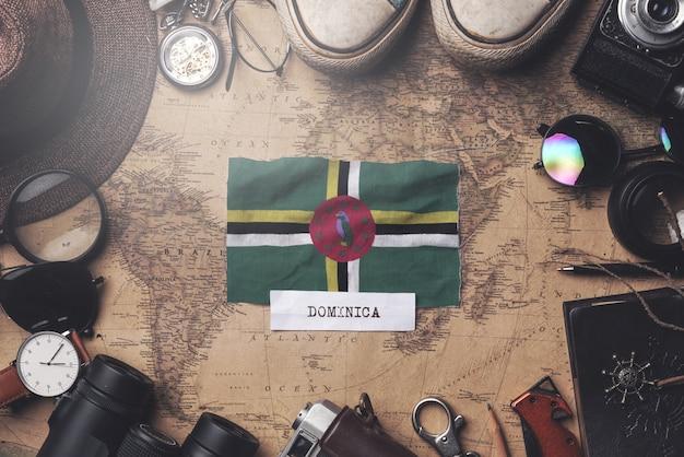 Bandeira de dominica entre acessórios do viajante no mapa antigo do vintage. tiro aéreo