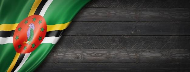 Bandeira de dominica na parede de madeira preta