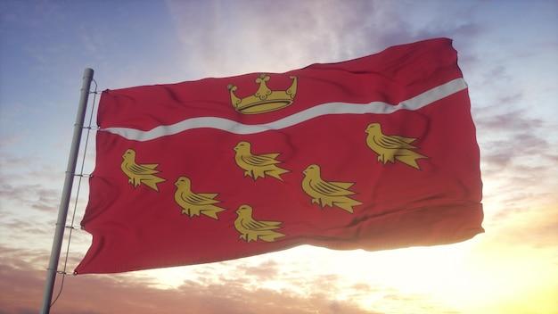 Bandeira de east sussex, inglaterra, balançando ao vento, o céu e o sol de fundo. renderização 3d