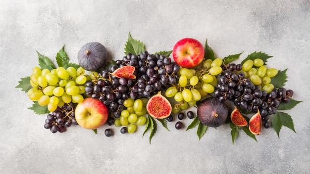 Bandeira de frutas frescas de outono. uvas pretas e verdes, figos e folhas em uma mesa cinza