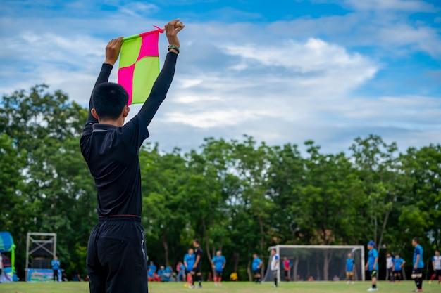 Bandeira de futebol na mão do árbitro assistente de futebol