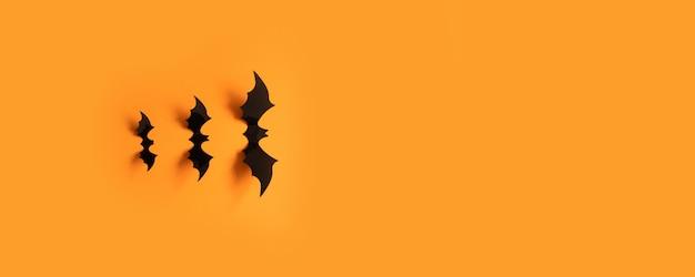 Bandeira de halloween com bastões pretos em uma superfície alaranjada, vista superior.