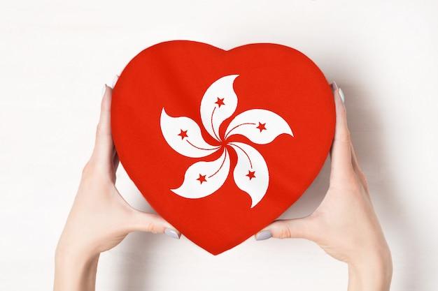 Bandeira de hong kong em uma caixa em forma de coração nas mãos femininas