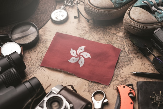 Bandeira de hong kong entre acessórios do viajante no antigo mapa vintage. conceito de destino turístico.