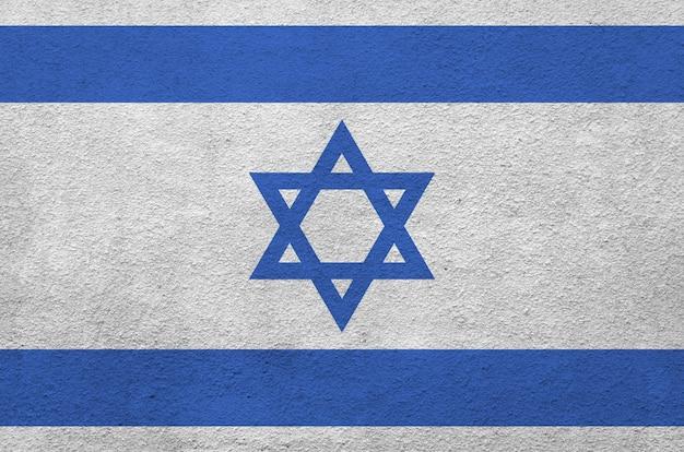 Bandeira de israel retratada em cores brilhantes de tinta na parede de reboco em relevo antigo.
