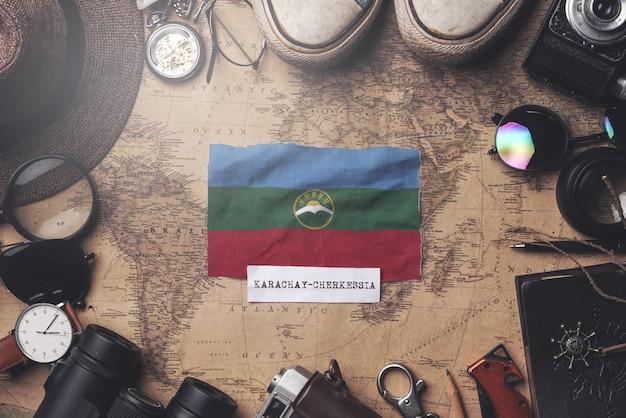 Bandeira de karachay-cherkessia entre acessórios do viajante no mapa antigo do vintage. tiro aéreo