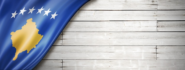 Bandeira de kosovo na velha parede branca. banner panorâmico horizontal.