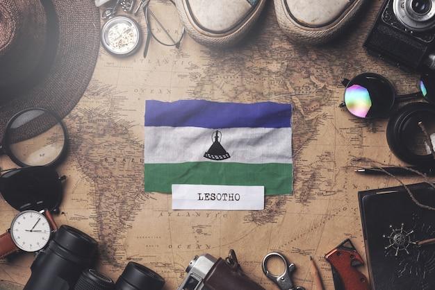 Bandeira de lesoto entre acessórios do viajante no mapa antigo do vintage. tiro aéreo